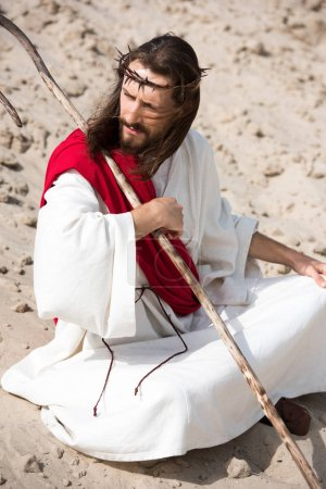 Jesus in robe, red sash and crown of thorns sitting in lotus position on sand in desert and looking away