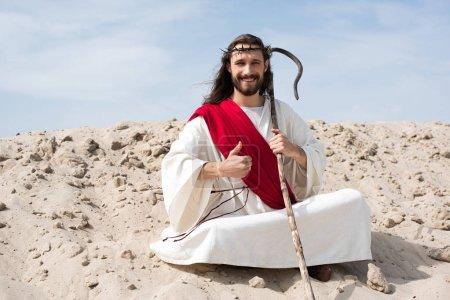Photo pour Souriant, Jésus assis en position du lotus sur le sable, holding personnel et montrant le pouce vers le haut dans le désert - image libre de droit