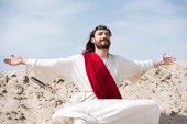 Jesus in robe, red sash and crown of thorns sitting in lotus position with open arms and closed eyes in desert