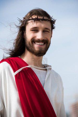 Photo pour Portrait de sourire Jésus en robe, écharpe rouge et Couronne d'épines à l'extérieur - image libre de droit