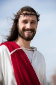 portrait of smiling Jesus in robe, red sash and crown of thorns outdoors