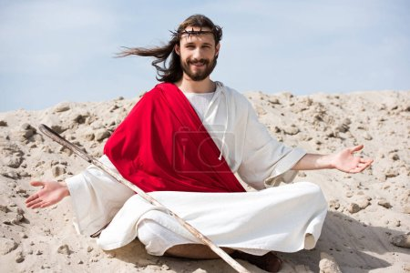 smiling Jesus in robe, red sash and crown of thorns sitting in lotus position with open arms on sand in desert