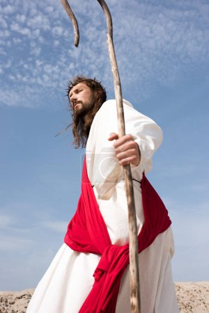low angle view of Jesus in robe, red sash and crown of thorns walking in desert with staff
