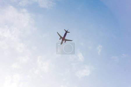 low angle view of plane flying in blue cloudy sky