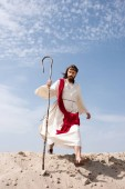 Jesus in robe, red sash and crown of thorns walking in desert with staff