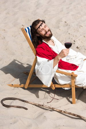 smiling Jesus in robe and red sash resting on sun lounger with glass of red wine in desert