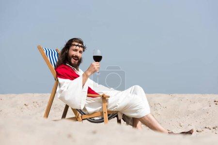 Photo pour Jésus souriant en robe et écharpe rouge au repos sur les transats avec verre de vin rouge dans le désert, en regardant la caméra - image libre de droit
