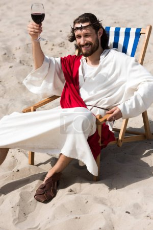 cheerful Jesus in robe and red sash resting on sun lounger and showing glass of red wine in desert