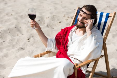 smiling Jesus resting on sun lounger with glass of wine and talking by smartphone in desert