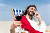 happy Jesus resting on sun lounger with glass of wine and talking by smartphone in desert