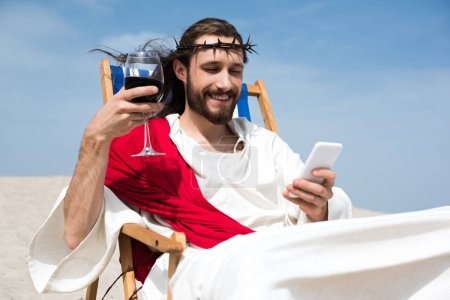smiling Jesus resting on sun lounger with glass of wine and using smartphone in desert