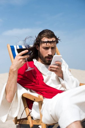 surprised Jesus resting on sun lounger with glass of wine and looking at smartphone in desert