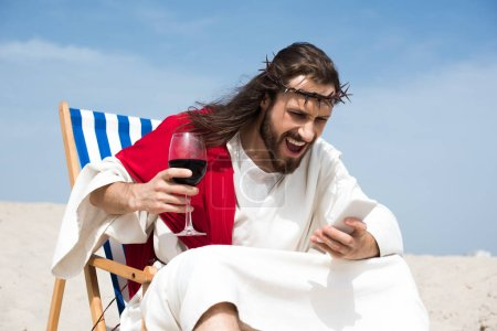 angry Jesus resting on sun lounger with glass of wine and screaming at smartphone in desert