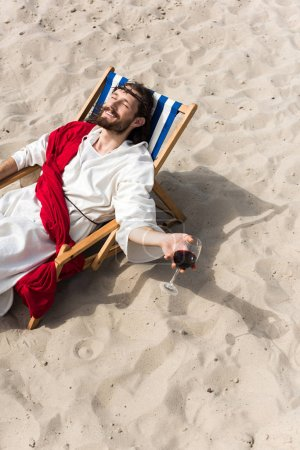 high angle view of happy Jesus in robe and red sash relaxing on sun lounger with glass of red wine in desert