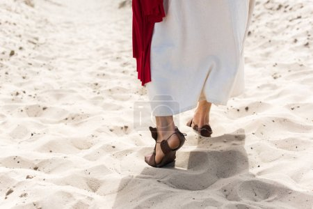 cropped image of Jesus in robe, sandals and red sash walking on sand in desert