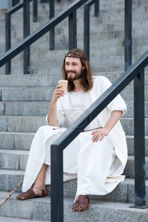 smiling Jesus in robe and crown of thorns sitting on stairs and holding disposable coffee cup on street