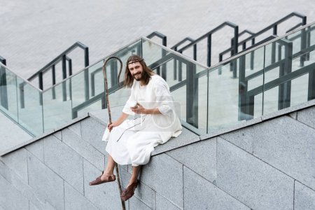 smiling Jesus in robe and crown of thorns sitting on staircase side and holding coffee in paper cup