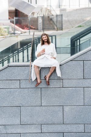 cheerful Jesus in robe and crown of thorns sitting on staircase side and holding coffee to go