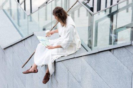 Photo pour Jésus dans la robe et la Couronne d'épines, assis à côté de l'escalier, en tenant la tasse à café jetable et en regardant de carte - image libre de droit