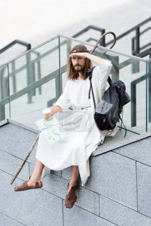 Jesus in robe and crown of thorns sitting on staircase side, holding disposable coffee cup and map, looking away