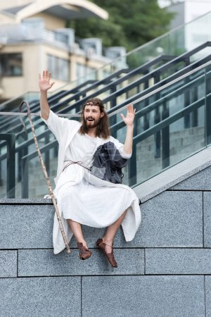 happy Jesus in robe and crown of thorns sitting on staircase side and waving hands