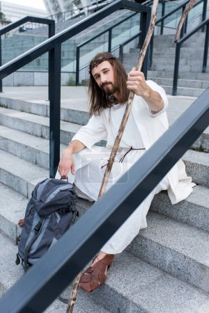 Jesus in robe and crown of thorns sitting on stairs with travel bag and staff, looking at camera
