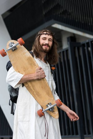 low angle view of cheerful Jesus in robe and crown of thorns holding skateboard