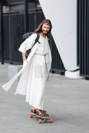 smiling Jesus in robe and crown of thorns skating on longboard on street