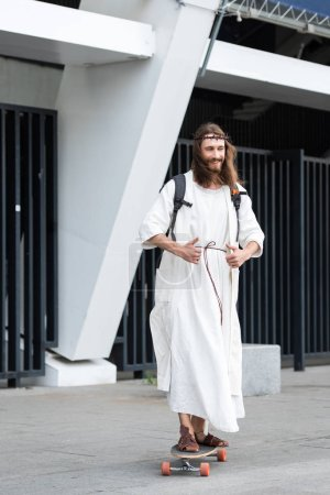 smiling Jesus in robe and crown of thorns skating on longboard on street and showing thumbs up