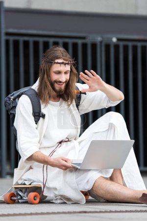 smiling Jesus in robe and crown of thorns sitting on skateboard and waving hand during video call