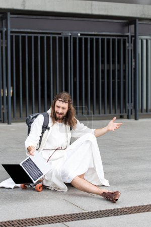irritated Jesus in robe and crown of thorns sitting on skateboard and gesturing to laptop with blank screen in city