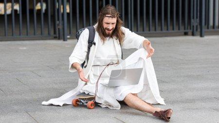 irritated Jesus sitting on skateboard and gesturing to laptop on street