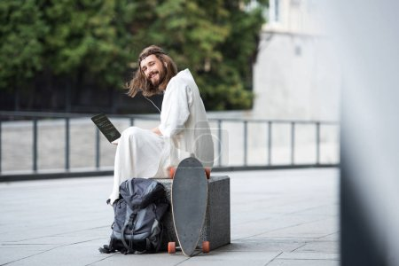 Jesus in robe and crown of thorns sitting on stone and holding laptop with html code on street