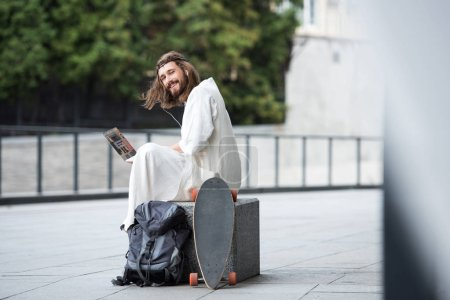 Jesus in robe and crown of thorns sitting on stone and using laptop with online booking website on street