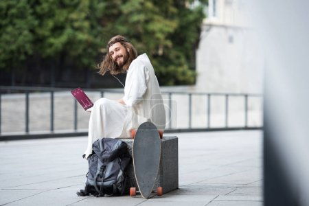 Jesus in robe and crown of thorns sitting on stone and using laptop with medical appliance on street