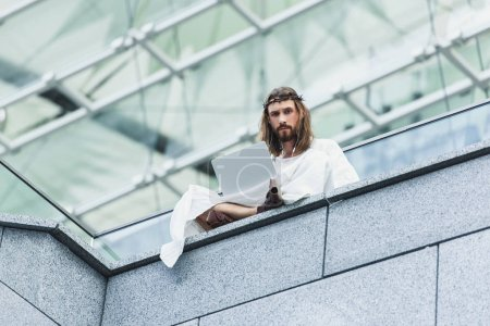 low angle view of serious Jesus in robe and crown of thorns using laptop while sitting on wall