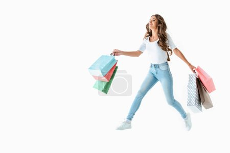 attractive happy girl jumping with shopping bags, isolated on white