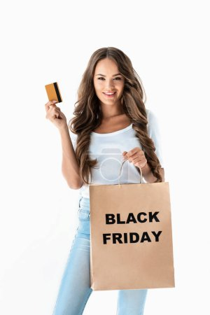 beautiful young woman holding golden credit card and shopping bag with black friday sign, isolated on white