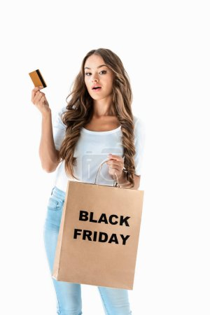 surprised girl holding golden credit card and shopping bag with black friday sign, isolated on white