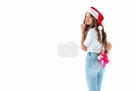 attractive girl in santa hat hiding christmas present and showing silence symbol, isolated on white