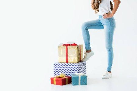 vue recadrée de femme debout près de boîtes-cadeaux, isolé sur blanc