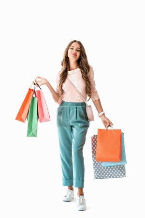 Photo for Attractive happy girl posing with colorful shopping bags, isolated on white - Royalty Free Image
