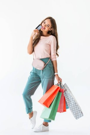 Photo pour Belle jeune fille souriante, détenant la carte de crédit et les sacs à provisions, isolés sur blanc - image libre de droit