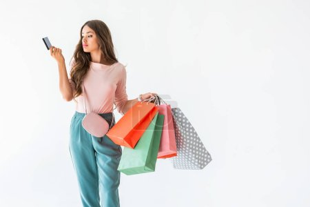 beautiful girl holding credit card and shopping bags, isolated on white