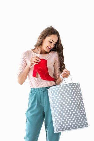 Photo for Smiling girl with shopping bag and red shoe, isolated on white - Royalty Free Image