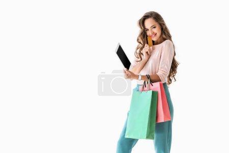 Photo pour Jeune femme souriante avec des sacs à provisions shopping en ligne avec tablette et carte de crédit, isolé sur blanc - image libre de droit