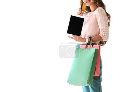 Foto de Vista recortada de chica con bolsas de compras en línea con tablet y tarjeta de crédito, aislado en blanco - Imagen libre de derechos