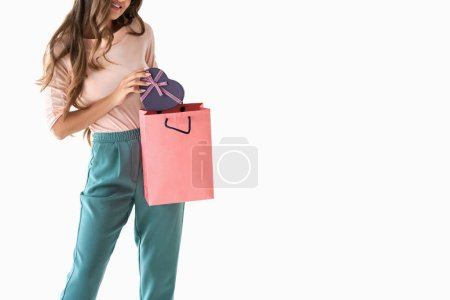 cropped view of attractive girl with shopping bag and heart shaped gift box, isolated on white
