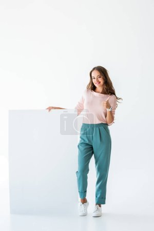beautiful young woman standing with empty board and showing thumb up, isolated on white