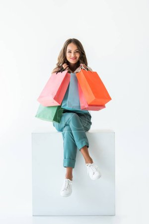 Photo for Smiling shopaholic sitting on white cube with shopping bags, isolated on white - Royalty Free Image